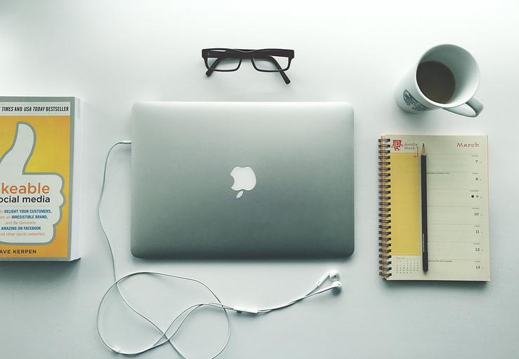 Macbook na bielom stole, žltá kniha, notes a káva, dioptrické okuliare a slúchadlá.jpg