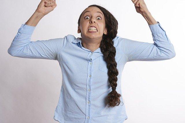 Žena v modrej blúzke má ruky zovreté v päť a kričí.jpg