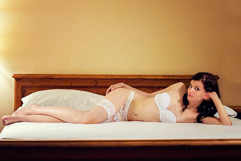 Čiernovlasá žena v erotickej bielizni na posteli.jpg
