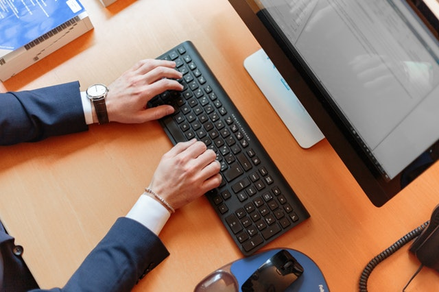 Muž v obleku píše na klávesnici položenej na hnedom stole.jpg